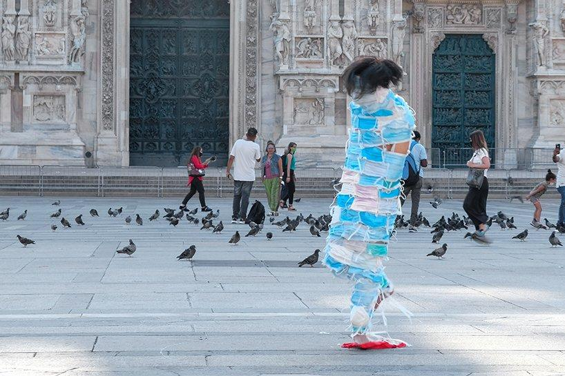 man wrapped by face masks struggles to move in no escape performance in milan, italy