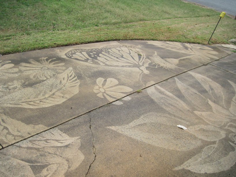 dianna wood uses power washer to create art on her dirty driveway